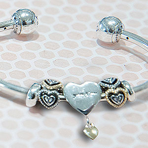 PANDORA charm bracelet on spotted background.